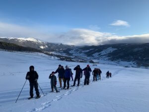people walking in line on snowshoes