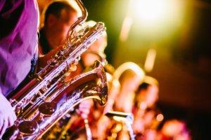 bilde viser saxofon og blurry folk i bakgrunnen