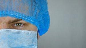 man med munnbind og operasjonshat