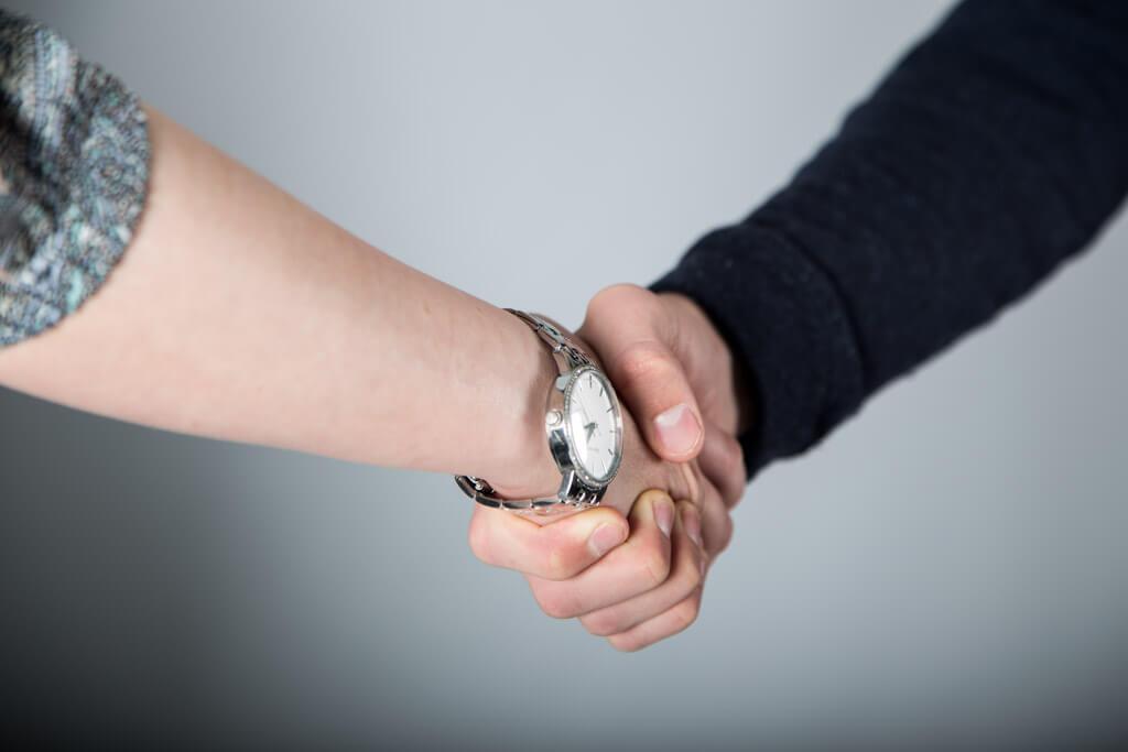 tar hverandre i hånden for å bekrefte avtalen